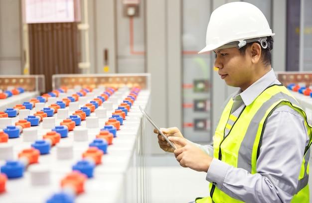 Sistema de sala de control solar inverter y almacenamiento de baterías. ingeniero electricista que supervisa el controlador de carga solar y registra los datos en la aplicación móvil en una tableta digital.
