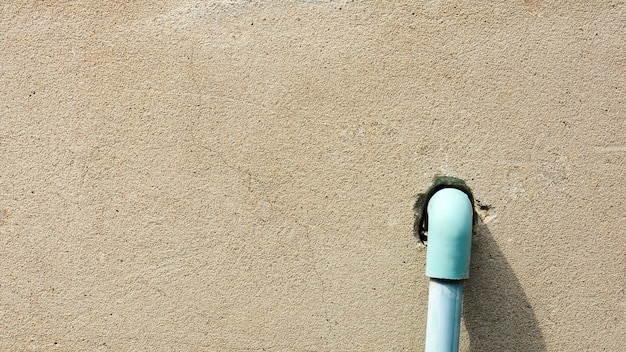 El sistema de tuberías de agua de plástico azul se instala en el viejo muro de concreto marrón