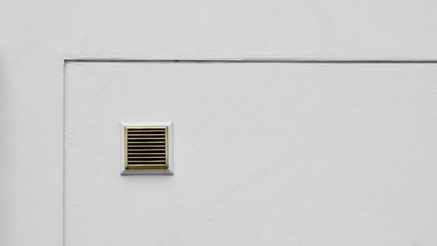Sistema de ventilación en pared de cemento blanco.