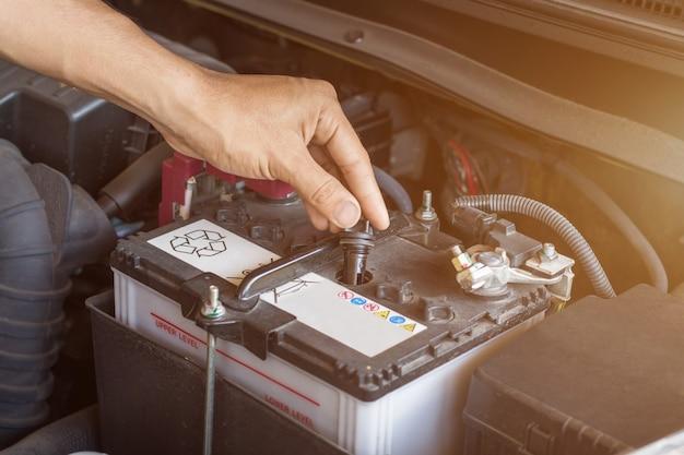 El sistema de verificación de funcionamiento del mecánico de automóviles y el agua de la batería llenan el motor de un automóvil viejo en la estación de servicio, cambian y reparan antes de conducir