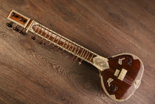 Sitar instrumento musical indio tirado en el piso de madera