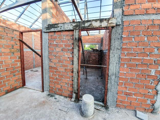 Sitio de construcción de la casa utilice ladrillos rojos como pared. con estructura de techo de acero pilar de hormigón.
