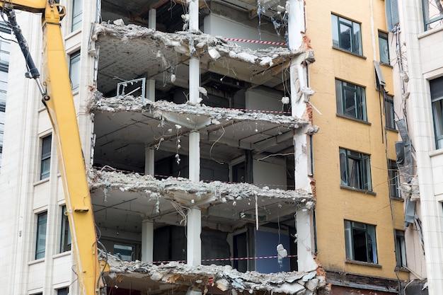 Sitio de construcción, demolición de casas en la antigua ciudad europea. obras de grúa con edificio en el centro, ingeniería urbana
