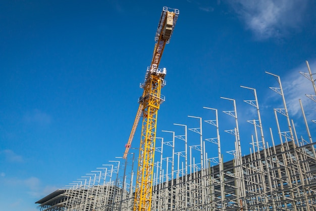 Sitio de la construcción de edificios con grúa contra el cielo azul.
