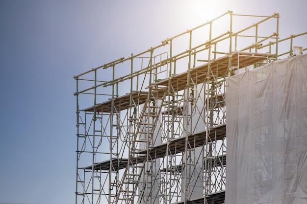 Sitio de construcción con torre de andamio y edificio de etiqueta de advertencia con cielo, andamios para fábrica de construcción