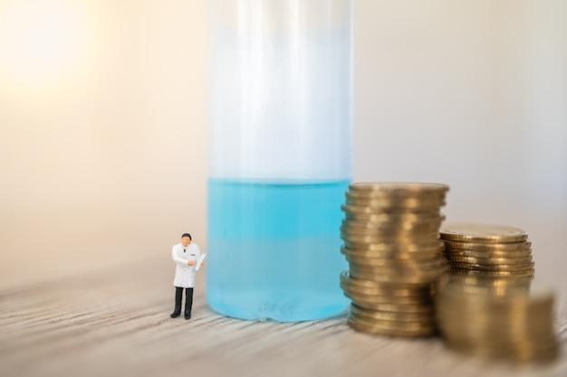 Situación de coronavirus (covid-19) cocept de negocios y economía. doctor figura miniatura personas con portapapeles paciente de pie con pila de monedas de oro con gel de alcohol desinfectante