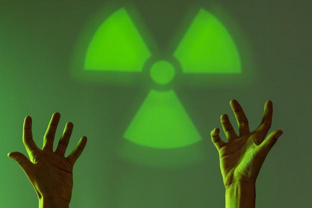 Situación desesperada. las manos masculinas tocan el signo de peligro de radiación. fondo verde copia espacio