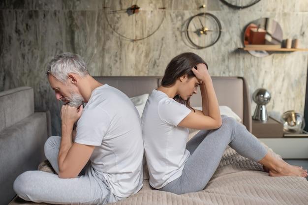 Situación difícil. se alejó ofendido triste hombre adulto y mujer joven sentada en la cama espalda con espalda
