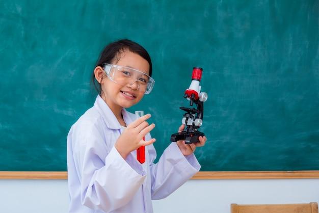 Situación y sonrisa asiáticas jovenes del estudiante en sala de clase de la ciencia