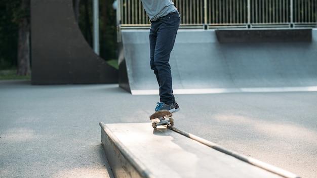 Skateboarding. vida activa del hombre. chico en patineta en el parque. piernas en jeans.