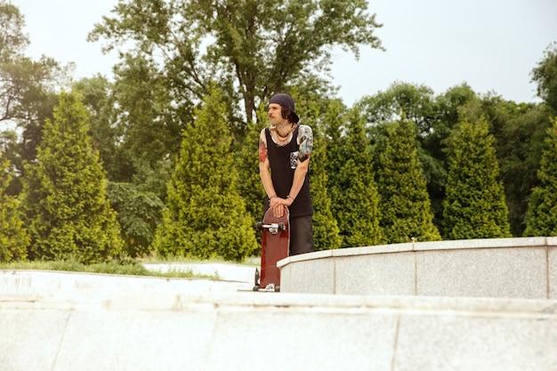 Skater descansando después de montar en la calle de la ciudad en un día nublado. hombre joven en zapatillas y gorra con un longboard sobre el asfalto. concepto de actividad de ocio, deporte, extremo, afición y movimiento.