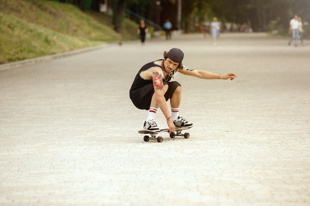 Skater haciendo un truco en la calle de la ciudad en un día nublado. hombre joven en zapatillas y gorra de montar y hacer longboard sobre el asfalto. concepto de actividad de ocio, deporte, extremo, afición y movimiento.