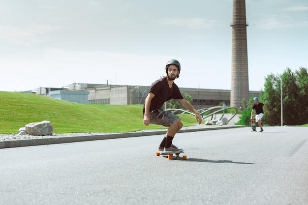 Skater haciendo un truco en la calle de la ciudad en un día soleado. hombre joven en equipo de equitación y longboard sobre el asfalto en acción. concepto de actividad de ocio, deporte, extremo, afición y movimiento.