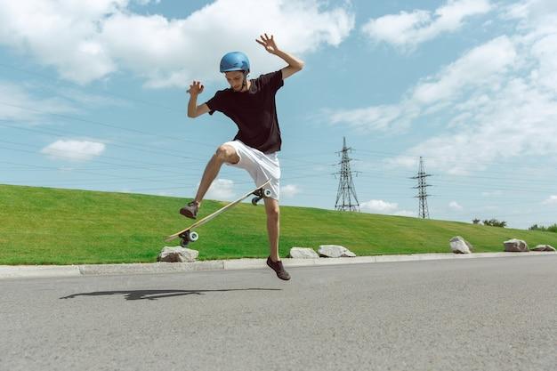 Skater haciendo un truco en la calle de la ciudad en un día soleado. joven en equipo de equitación y longboard cerca de pradera en acción. concepto de actividad de ocio, deporte, extremo, afición y movimiento.