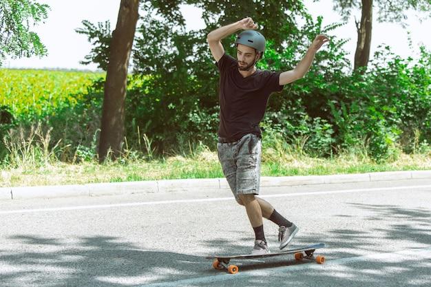 Skater haciendo un truco cerca de la pradera en un día soleado. hombre joven en equipo de equitación y longboard sobre el asfalto en acción. concepto de actividad de ocio, deporte, extremo, afición y movimiento.