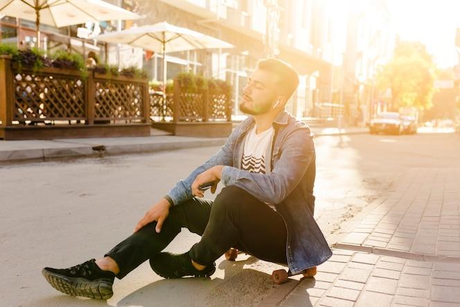 Skater masculino sentado en patineta escuchando música