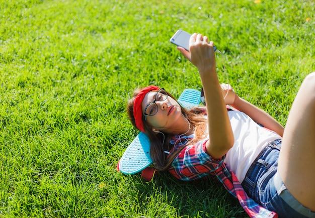 Skater de mujer con estilo divertido con patín tumbado en la hierba verde y escuchando música en auriculares en un día soleado