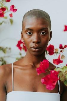 Skinhead mujer rodeada de flores rojas.