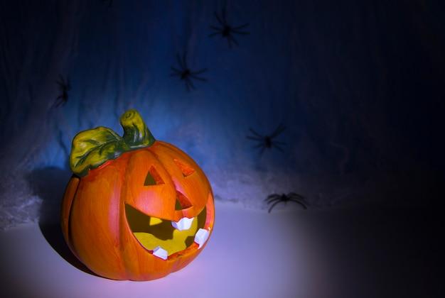 Skull head y halloween pumpkin head of horrors frotar están cubiertos con una telaraña