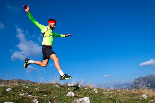 Skyrunner durante un salto cuesta abajo en prados de montaña