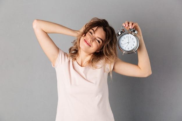 Sleepy mujer sonriente en camiseta despierta mientras sostiene el despertador y sobre gris