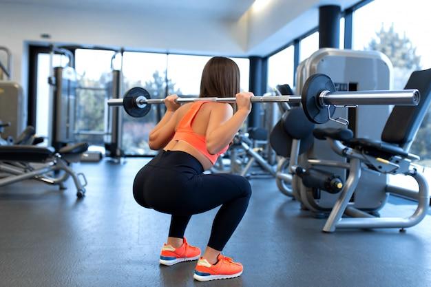 Slim apuesto joven en ropa deportiva se pone en cuclillas con una barra en el hombro en el gimnasio