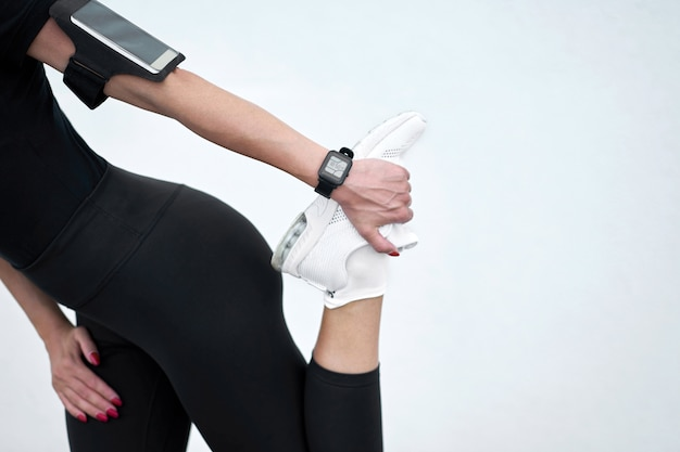 Slim chica vistiendo ropa deportiva negra que se extiende sobre fondo de pared blanca