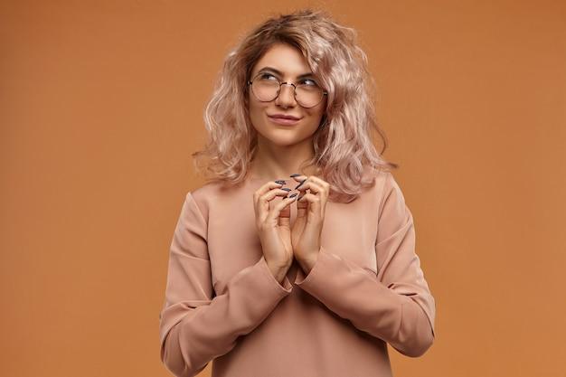 Sly hipster girl planeando una broma o un truco malvado, uniendo las manos y sonriendo misteriosamente. mujer joven astuta pensativa en gafas con plan complicado en mente