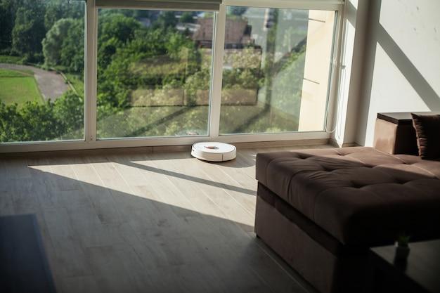Smart house, el robot aspirador funciona en un piso de madera en una sala de estar,
