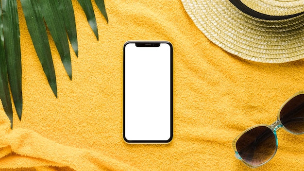 Smartphone y accesorios de playa sobre fondo claro.