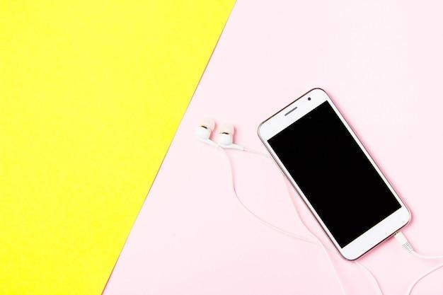 Smartphone con auriculares sobre fondo amarillo y rosa de arte