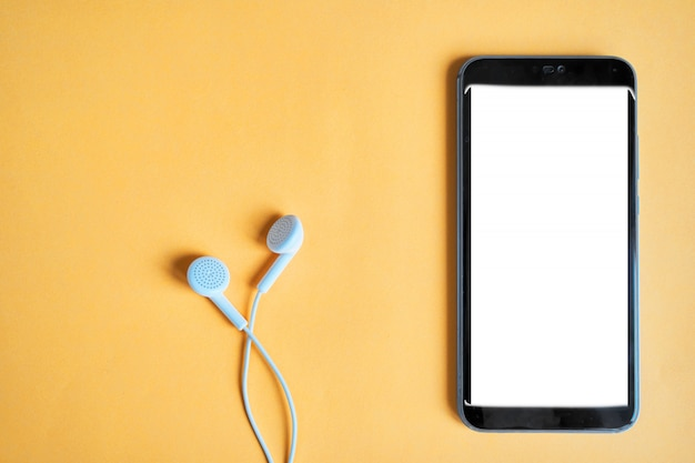 Smartphone y auriculares sobre un fondo brillante