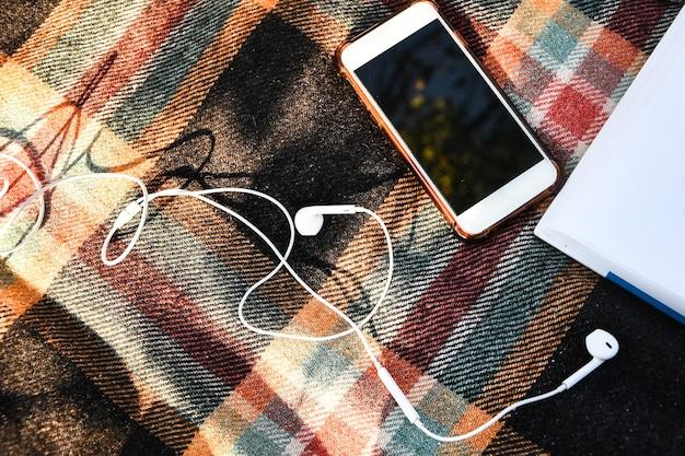 Smartphone con auriculares en los suéteres acogedores. vista superior. flatlay de otoño. podcasts de escucha al aire libre. luz de sol