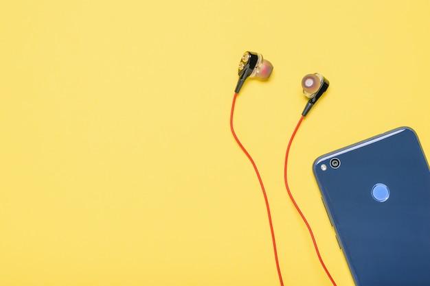 Smartphone azul con los auriculares rojos en fondo amarillo.