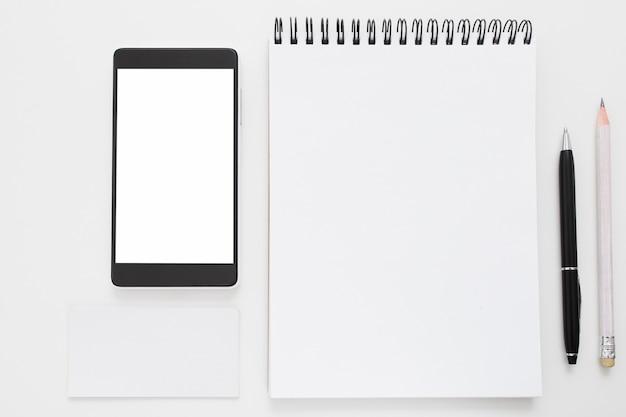 Smartphone y bloc de notas en blanco