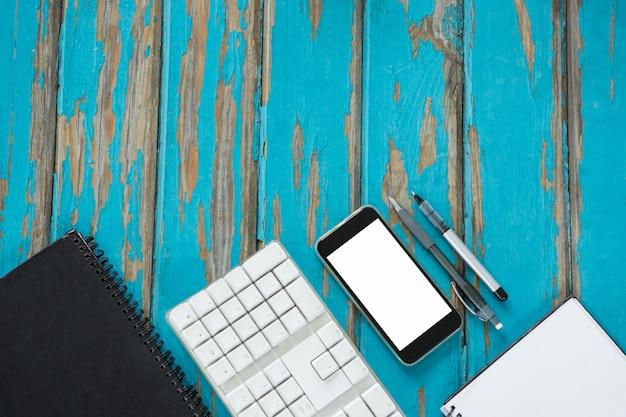 Smartphone, bloc de notas y teclado colocados juntos