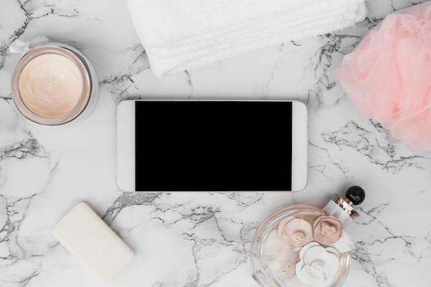 Smartphone; botella de perfume; toalla; jabón; crema hidratante y esponja vegetal sobre fondo de mármol.