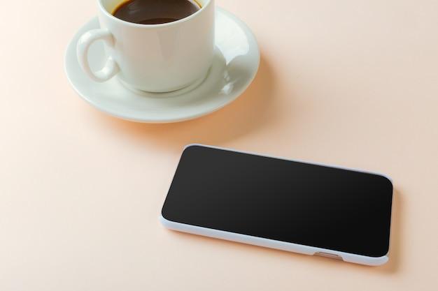 Smartphone y café en la mesa.