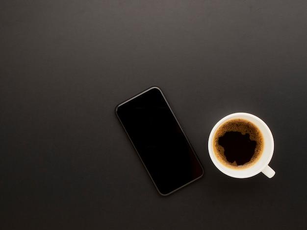 Smartphone y café sobre fondo negro.