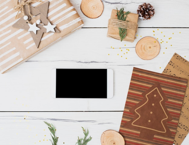 Smartphone entre cajas de regalo en envolturas y decoraciones navideñas.