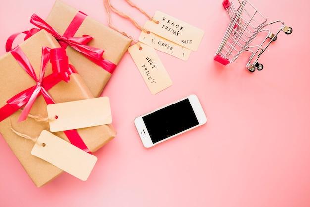 Smartphone cerca de carrito de compras y cajas de regalo.