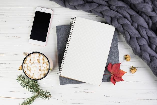 Smartphone cerca de rama de abeto, taza con malvaviscos y cuaderno