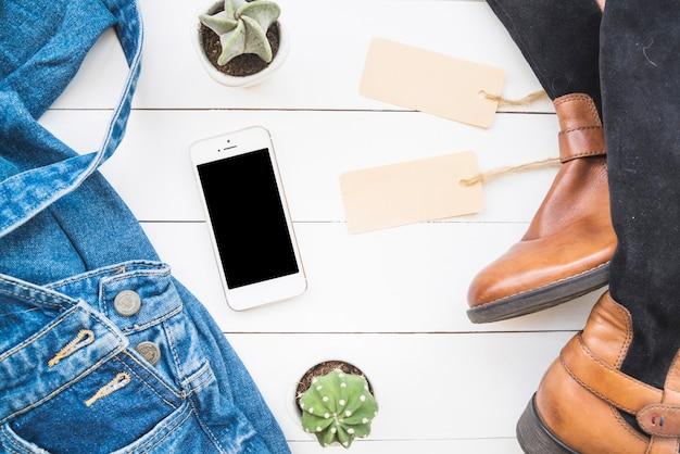 Smartphone cerca de tela de jean, botas altas con etiquetas y cactus.