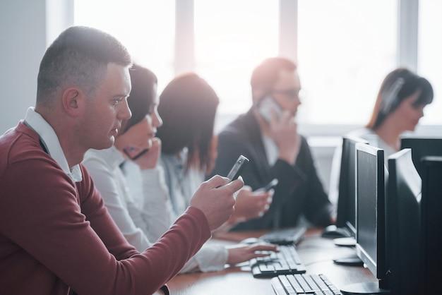 Smartphone de color negro. jóvenes que trabajan en el centro de llamadas. se acercan nuevas ofertas