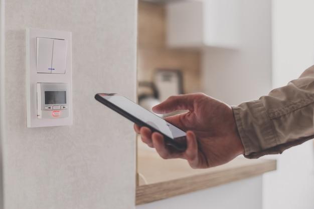 Smartphone conectado al controlador de calefacción por suelo radiante en la cocina. sistema de control remoto del hogar en un teléfono inteligente.