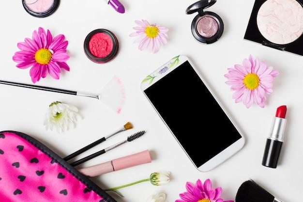Smartphone y cosmética decorativa en mesa de luz.