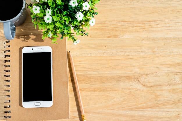 Smartphone en cuaderno, árbol de maceta, un lápiz y una taza de café sobre fondo de madera, vista superior con mesa de oficina.