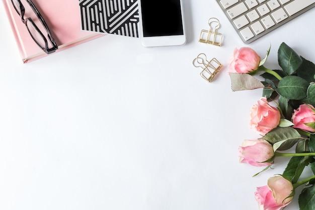 Smartphone, un cuaderno, un teclado, gafas y rosas rosadas sobre una superficie blanca