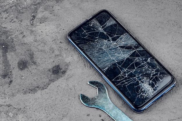 Smartphone estrellado con herramientas de reparación en gris