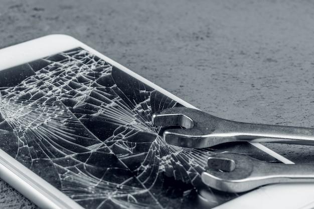 Smartphone estrellado con herramientas de reparación en pared gris